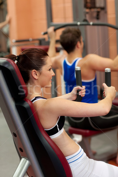 Radiant athletic woman using a shoulder press in a fitness center Stock photo © wavebreak_media
