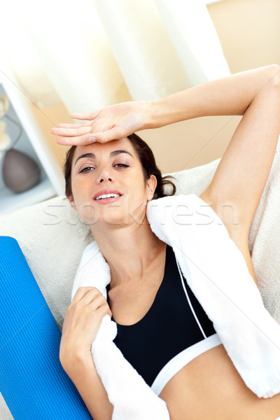 Exhausted hispanic woman sitting on the sofa after working out at home Stock photo © wavebreak_media