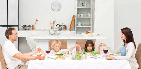 Concentrated family praying before having lunch in the kitchen Stock photo © wavebreak_media