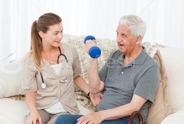 Lovely nurse helping her patient to do exercises Stock photo © wavebreak_media