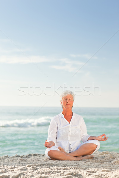 Mature woman practicing yoga on the beach Stock photo © wavebreak_media