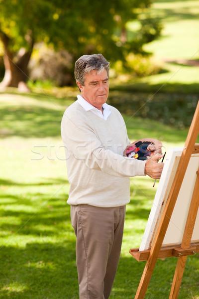 Elderly man painting in the park Stock photo © wavebreak_media