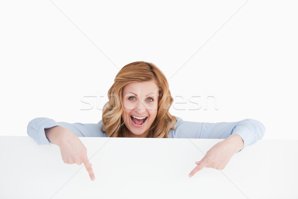 Happy blond-haired woman standing behind an empty white board while showing something Stock photo © wavebreak_media