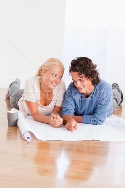 Portrait of a cute couple organizing their new home while lying on the floor Stock photo © wavebreak_media