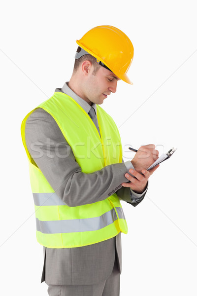 Portrait of a builder taking notes against a white background Stock photo © wavebreak_media