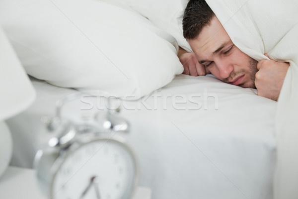 Young man covering his ears while his alarm clock is ringing in his bedroom Stock photo © wavebreak_media