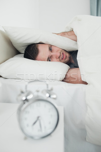 Portrait of a tired young man covering his ears while his alarm clock is ringing in his bedroom Stock photo © wavebreak_media