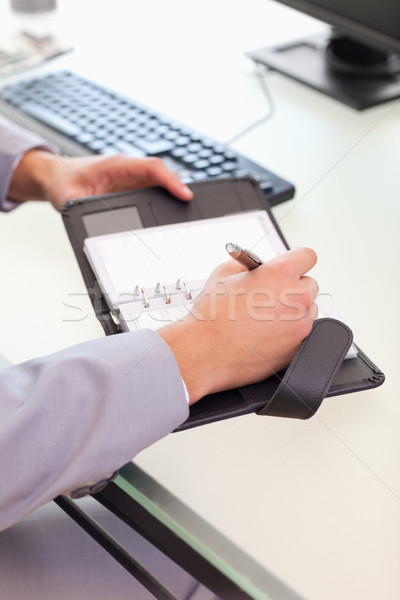 Young businessman taking notes on his pocket calender Stock photo © wavebreak_media
