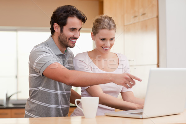 Couple using a notebook while having coffee in their kitchen Stock photo © wavebreak_media
