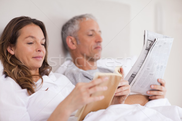 Woman reading a book while her husband is reading the news in their bedroom Stock photo © wavebreak_media