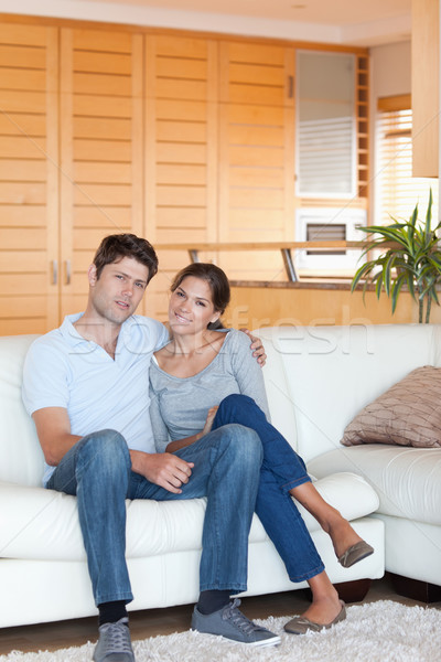 Portrait of a couple sitting on a couch while looking at the camera Stock photo © wavebreak_media