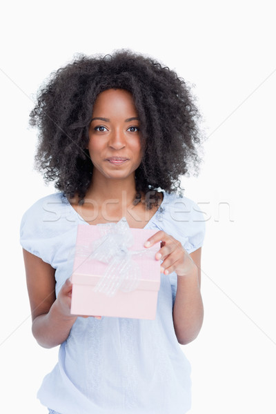 Woman looking at the camera after opening her gift against a white background Stock photo © wavebreak_media