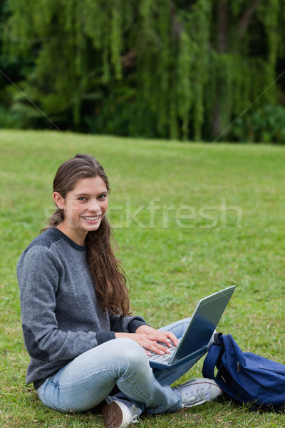 Student sitting cross-legged on the grass in the countryside while using her laptop Stock photo © wavebreak_media