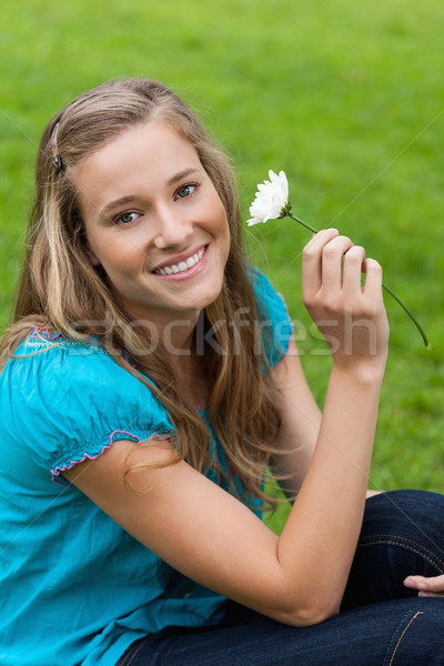 Young smiling woman holding a white flower while sitting down in the countryside Stock photo © wavebreak_media