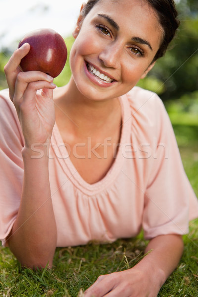 Woman smiles while holding a red apple as she is lying prone in grass Stock photo © wavebreak_media