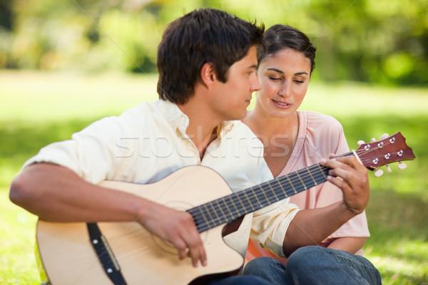 Mujer amigo jugar guitarra ambos sentarse Foto stock © wavebreak_media