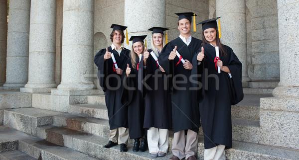 Five happy graduates posing the thumb-up in front of the university Stock photo © wavebreak_media
