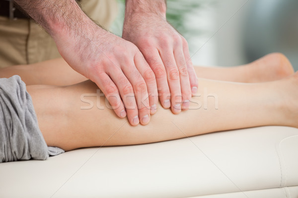 Woman lying forward while a man massaging her calf indoors Stock photo © wavebreak_media