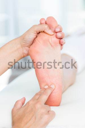 Two thumbs massaging a foot in a room Stock photo © wavebreak_media