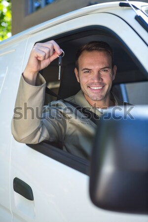 Smiling man holding car keys while sitting on a car Stock photo © wavebreak_media