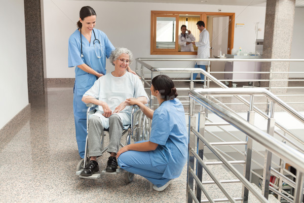 Two nurses talking with old women sitting in wheelchair and smiling Stock photo © wavebreak_media