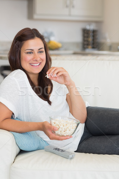 Woman eating popcorn while relaxing on the sofa and smiling Stock photo © wavebreak_media