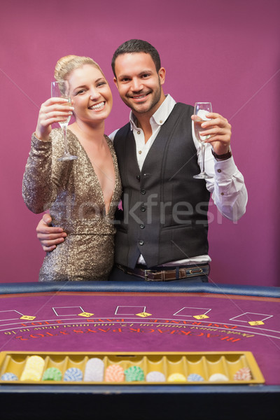 Two people standing at table in a casino while amusing and toasting Stock photo © wavebreak_media