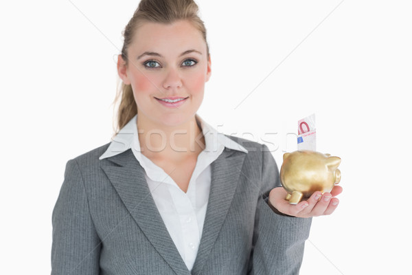 Businesswoman saving money with golden piggy bank in her hand Stock photo © wavebreak_media