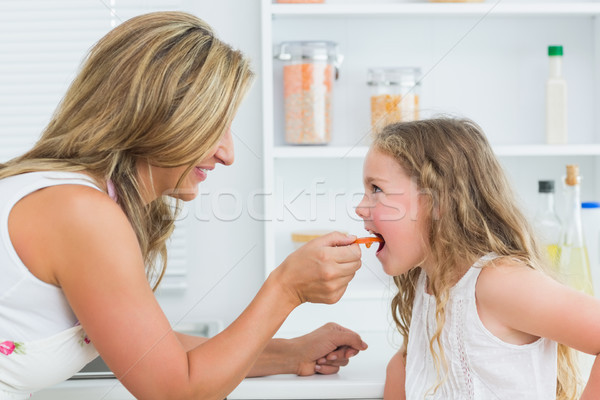 Smiling mother feeding daughter carrot in kitchen Stock photo © wavebreak_media