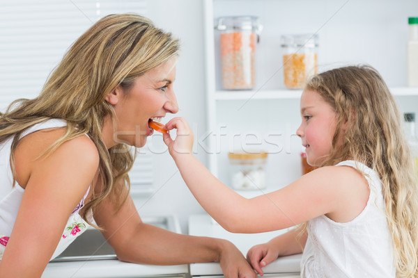 Daughter feeding mother carrot in the kitchen Stock photo © wavebreak_media