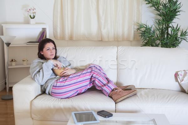 Kobieta popcorn puchar oglądania telewizja Zdjęcia stock © wavebreak_media