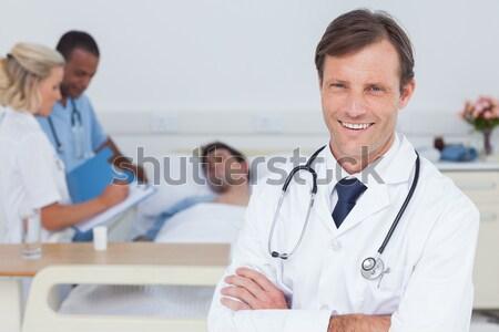 Doctor looking at phone with his team of nurses Stock photo © wavebreak_media
