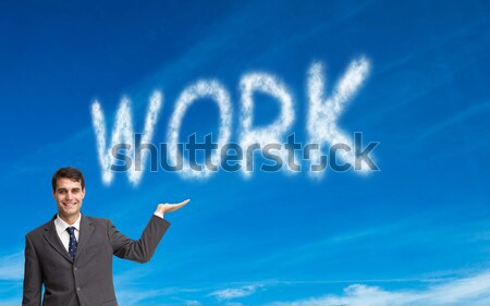 Stock photo: Businessman writing to do list on a blue wall