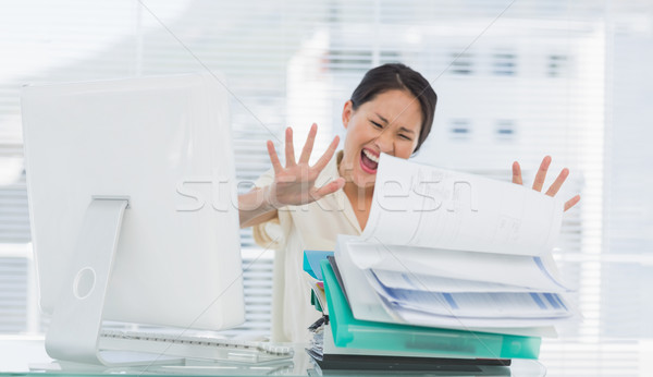 Businesswoman shouting with stack of folders at desk Stock photo © wavebreak_media