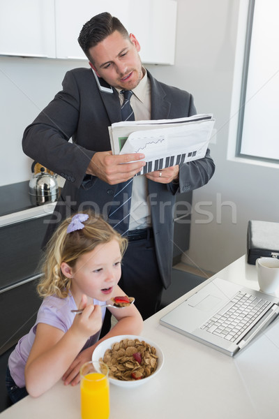 Businessman multi tasking while daughter having breakfast Stock photo © wavebreak_media
