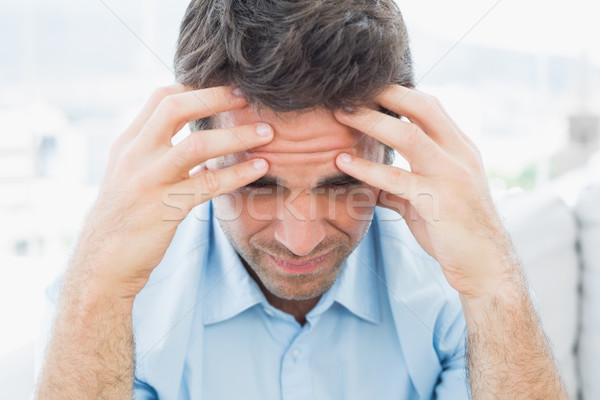 Attractive man sitting on the couch with headache Stock photo © wavebreak_media