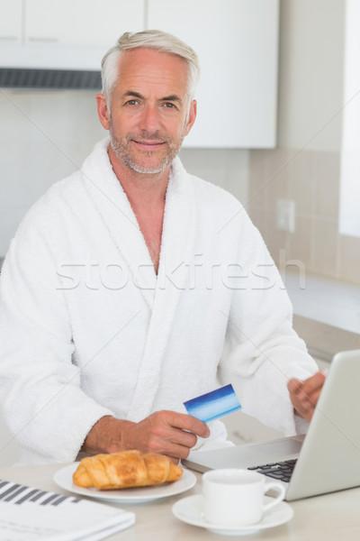Happy man shopping online at breakfast in a bathrobe Stock photo © wavebreak_media