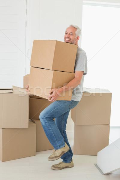 Smiling man carrying cardboard moving boxes Stock photo © wavebreak_media
