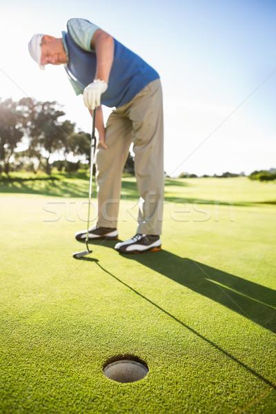 Golfer standing on the putting green watching hole Stock photo © wavebreak_media