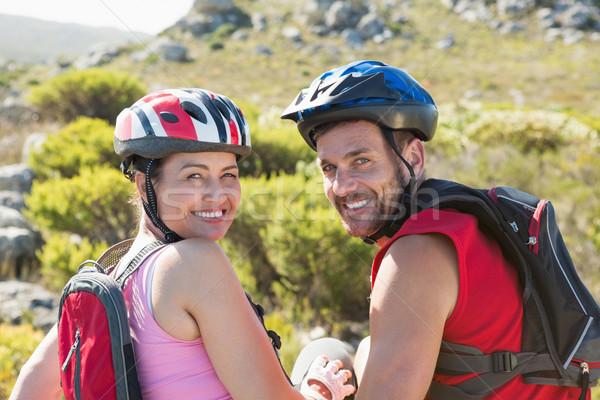 S'adapter cycliste couple séance souriant caméra Photo stock © wavebreak_media