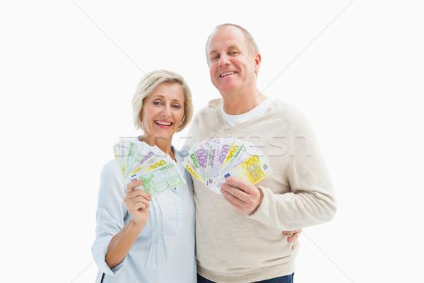 Happy mature couple smiling at camera showing money Stock photo © wavebreak_media
