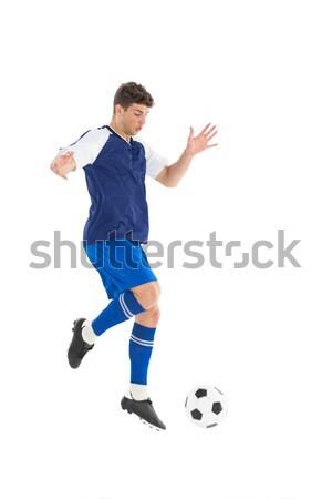 Football player in blue jersey kicking ball Stock photo © wavebreak_media
