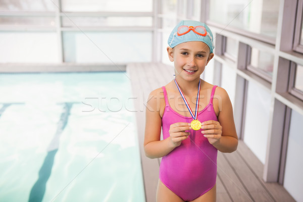 Cute little girl showing her swimming medal Stock photo © wavebreak_media