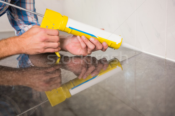 Stock photo: Plumber putting filling in between tiles