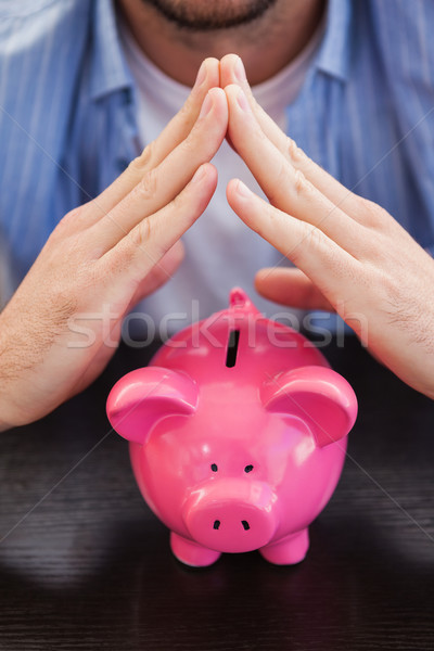 Casual man sheltering piggy bank Stock photo © wavebreak_media