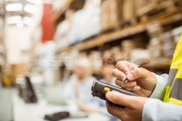 Close up of manager wearing yellow vest using handheld Stock photo © wavebreak_media