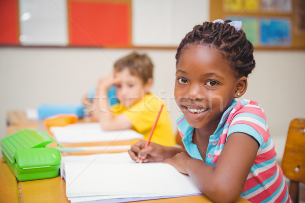 Cute pupils drawing at their desks one smiling at camera Stock photo © wavebreak_media