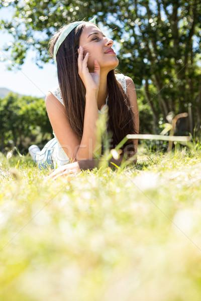Pretty brunette lying on the grass Stock photo © wavebreak_media