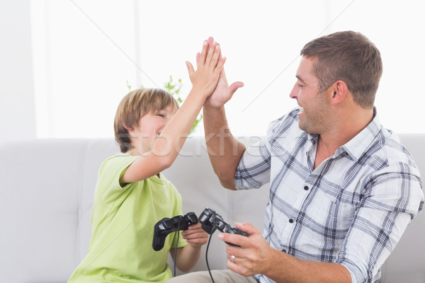 Father and son giving high-five while playing video game Stock photo © wavebreak_media