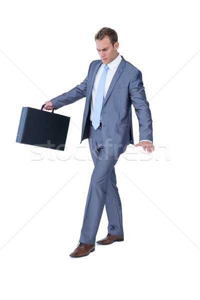 Stock photo: Businessman walking in equilibrium with suitcase